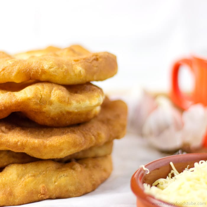 Langos is a Hungarian deep fried flat bread (made of yeast, flour & water) that is eaten while still warm. | happyfoodstube.com