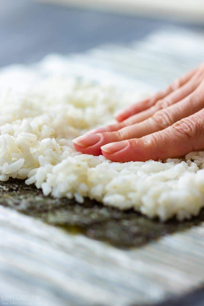 How to make Homemade Sushi Step 1 - Cover nori sheet with rice and press it down.