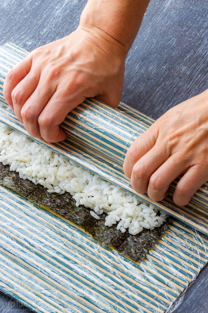 How to make Homemade Sushi Step 3 - Carefully roll it altogether with nori sheet over the fillings