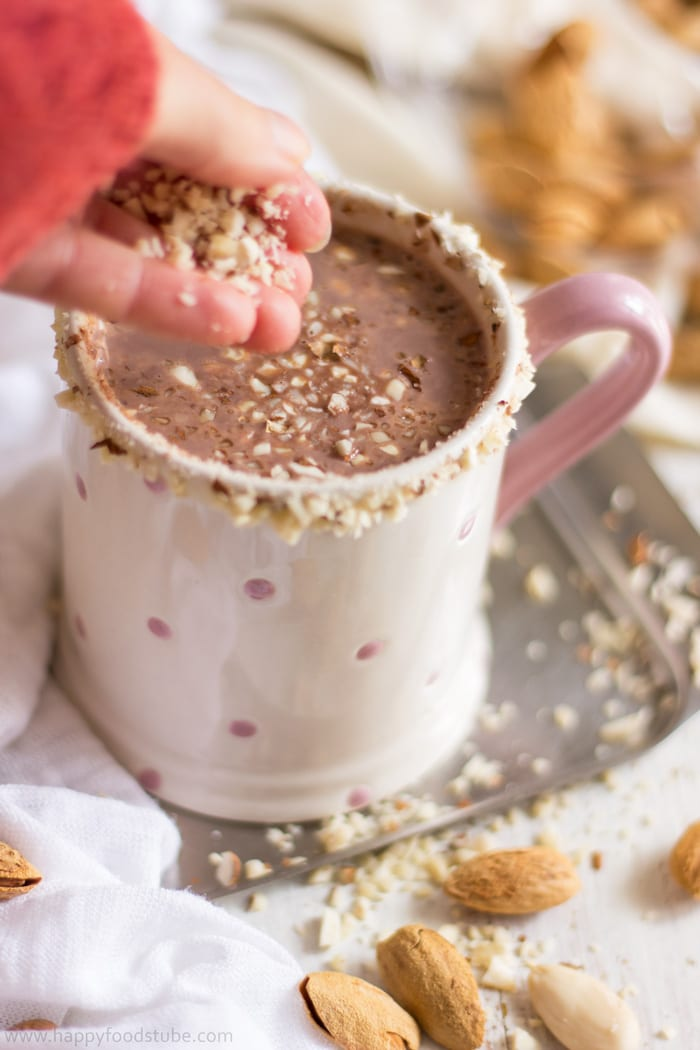 Topping hot cocoa with chopped almonds