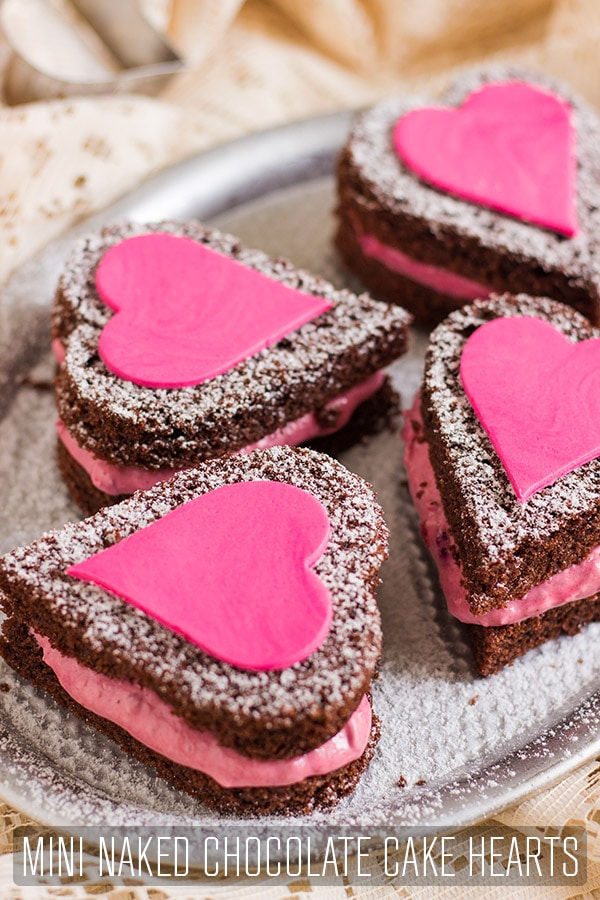 Mini Naked Chocolate Cake Hearts are perfect for Valentine's Day. Red wine chocolate cake with berry filling & decorated with fondant hearts. #happyfoodstube #valentines #chocolate #cake #recipe #valentinesday #love #dessert #hearts #baking