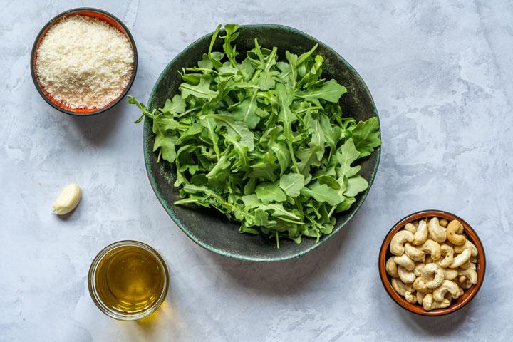 Ingredients for pesto - arugula, cashews, parmesan, garlic and olive oil
