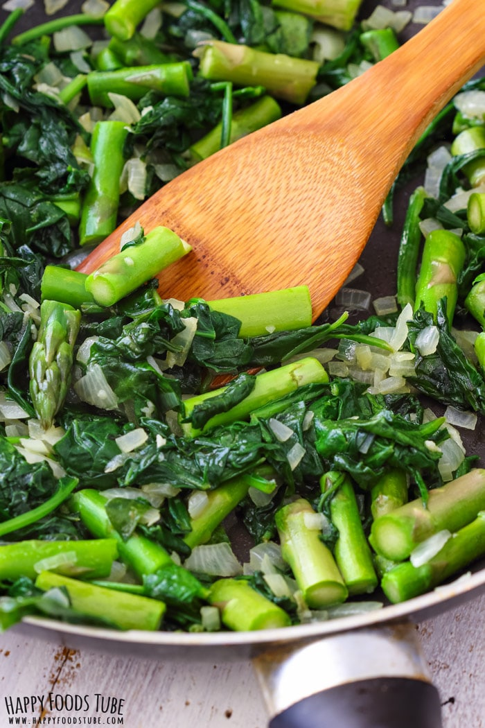 Cooking spinach and asparagus on the pan