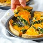 Spinach and Cheddar Quiche slice on hand