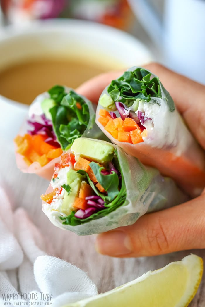 Three Vegetarian Fresh Spring Rolls with Peanut Sauce on the hand