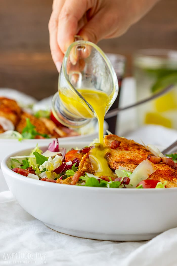Pouring honey mustard dressing to the Chicken Bacon Salad
