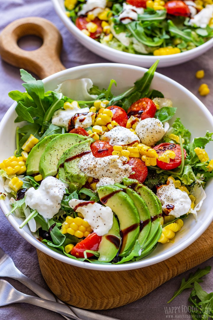 Burrata salad in a bowl with avocados, corn and tomatoes