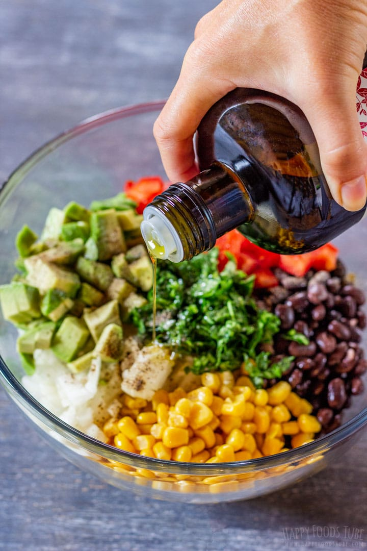 Making black bean and corn salad with olive oil