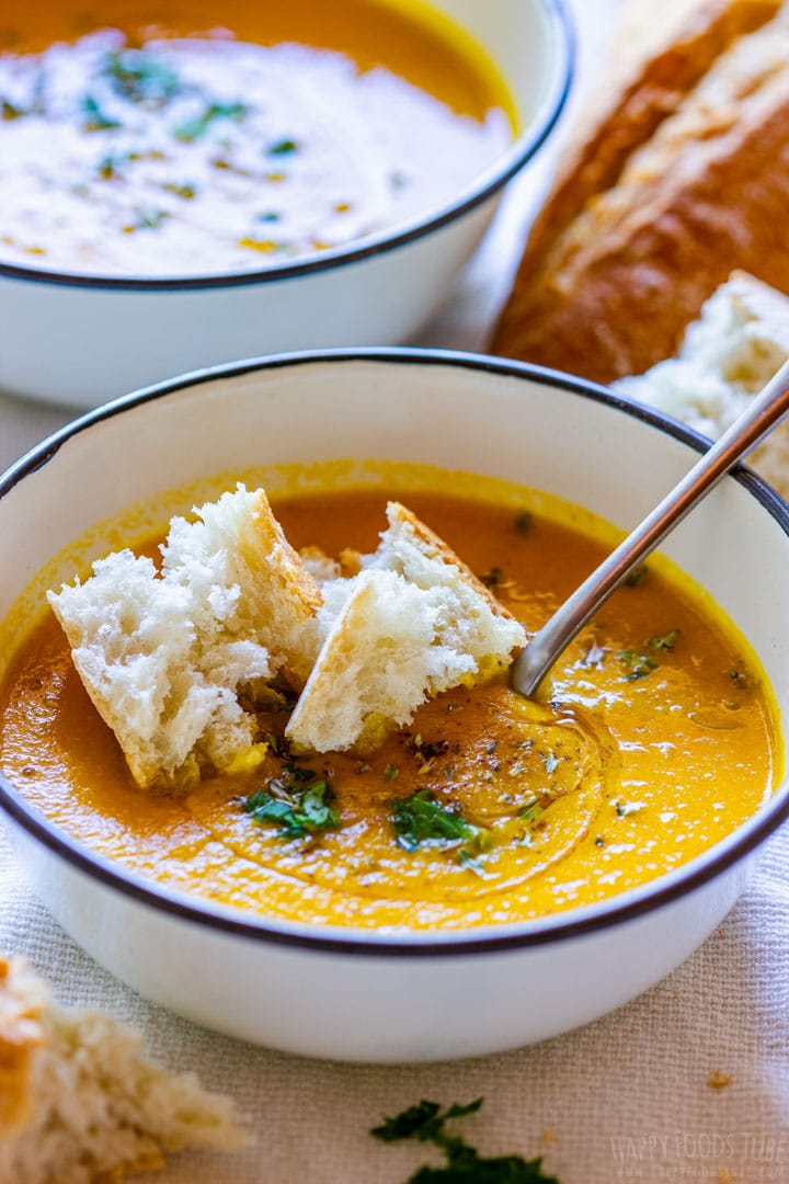 Homemade carrot soup in white bowl with bread