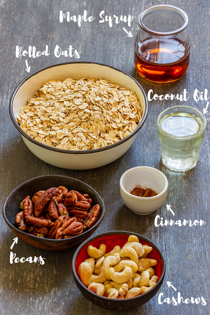 Rolled oats, pecans, cashews, cinnamon, coconut oil and maple syrup on the table