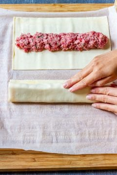 Unroll/unfold the puff pastry and cut in half (or thirds if too long). Top the center of each pastry sheet lengthwise with sausage filling. Brush one of the long edges with egg wash.