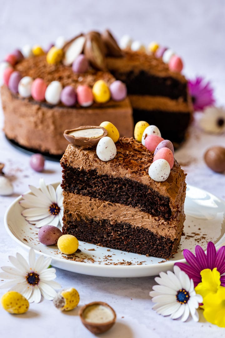 Slice of chocolate Easter cake with colorful mini Easter eggs