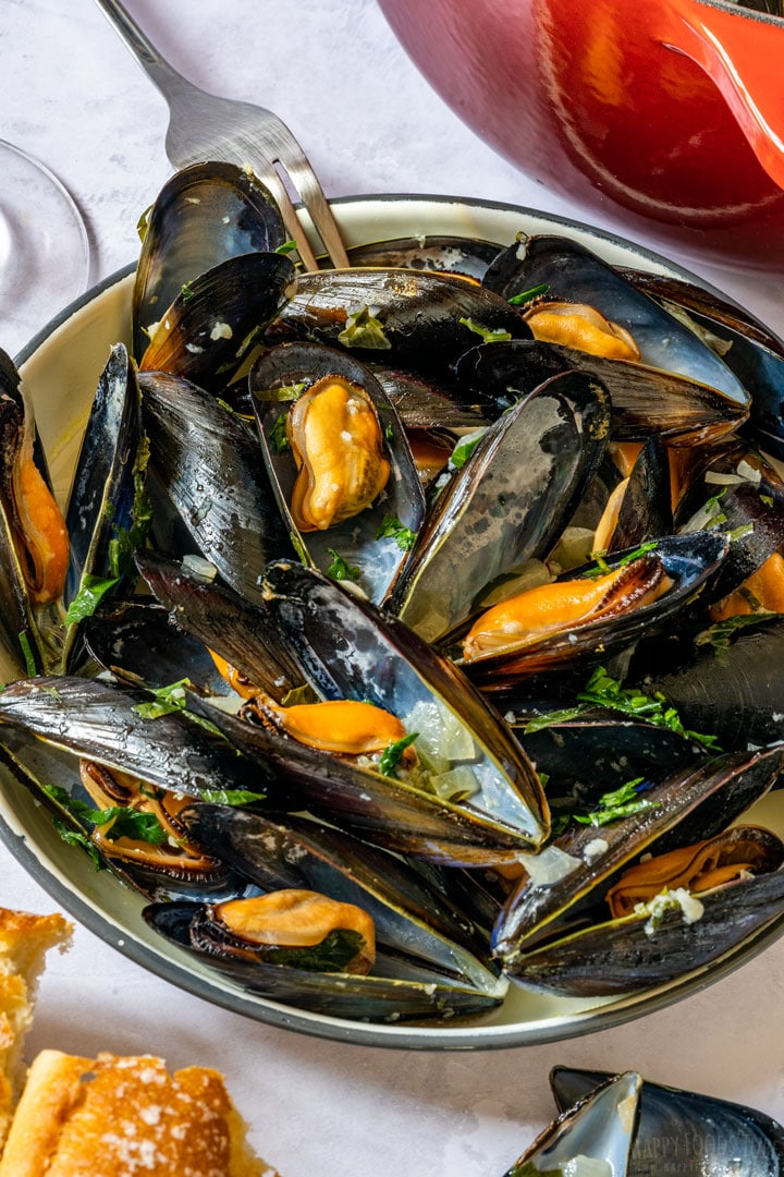Mussels in white wine on the plate with bread