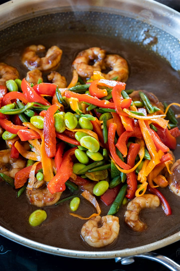 Cooking edamame beans, peppers, carrots and shrimp on a pan