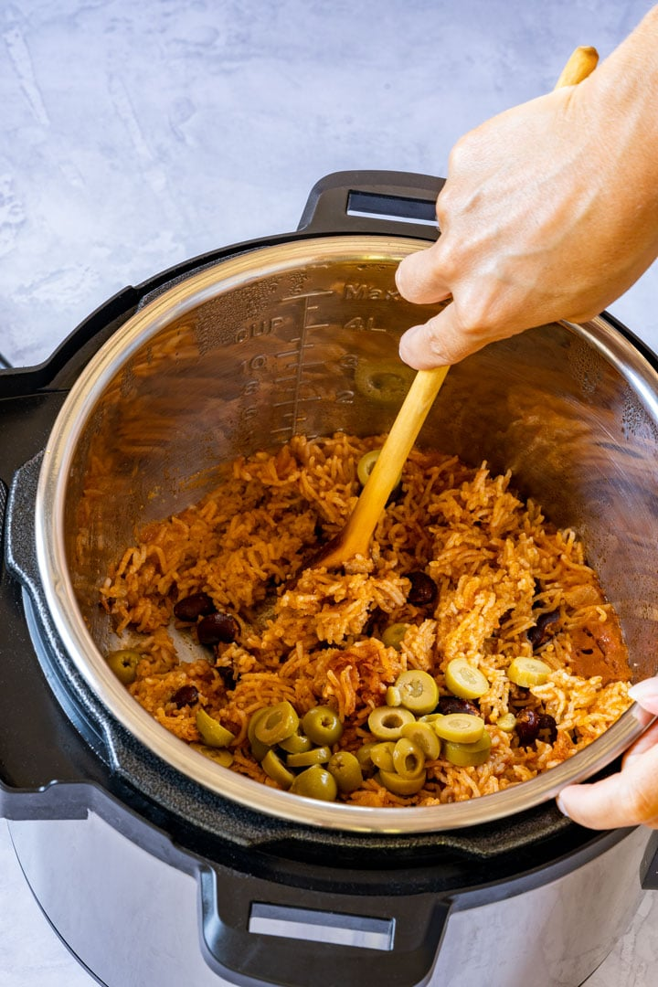 Mixing rice and beans with wooden spoon in an instant pot